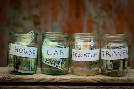 Glass jars with dollars and text: house,car, travel, education 스톡 콘텐츠