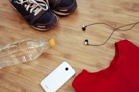 Sport equipment. Sneakers and water on wooden background