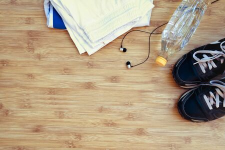 sports activities: Sport shoes and water with set for sports activities on wooden background.