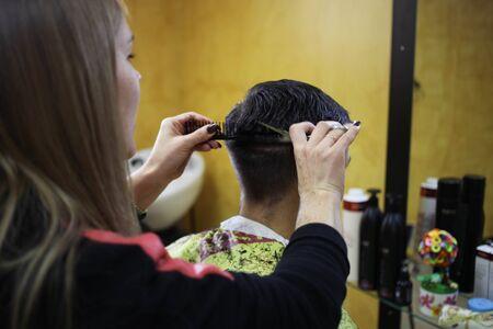 beauty parlour: Female hairdresser cutting hair of man client at beauty parlour