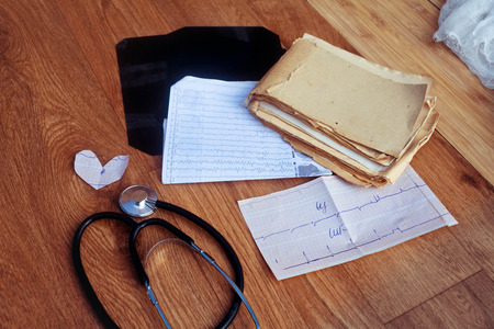 medical history: Medical history, ECG, X-rays, analyzes and stethoscope on the wooden background Stock Photo