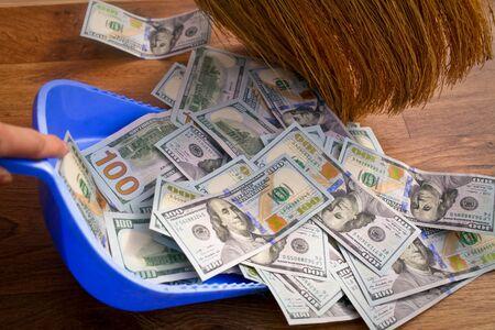 cleaning debt: Broom sweeps dollars in garbage scoop on wooden floor background