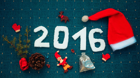 christamas: 2016 for New Year And Christmas design on  blue background  with fir leaves, Santas cap, cone and Santa, deer and mittens from plasticine Stock Photo