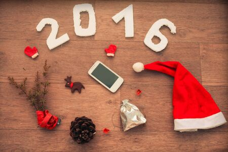 hogmanay: 2016 for New Year And Christmas design on  wooden table with fir leaves, smart phone, Santas cap and cone