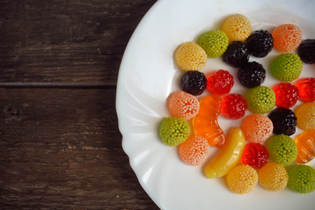 fruit jelly: Fruit jelly in the form of berries and fruit on a plate on a wooden background