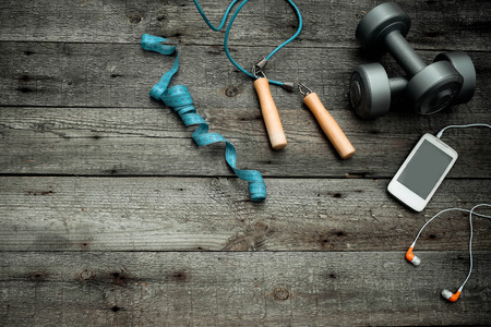 Sports equipment and the smartphone with earphones on a wooden background