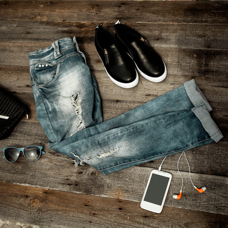 Fashionable ripped jeans, sunglasses, bag and footwear on a wooden background.