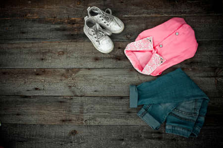 nurseries: Fashionable childrens jeans, blouse and footwear on a wooden background Stock Photo