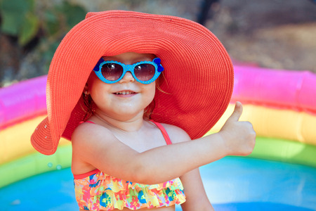 The beautiful little girl in a bathing suit and a hat swims in the pool Stock fotó