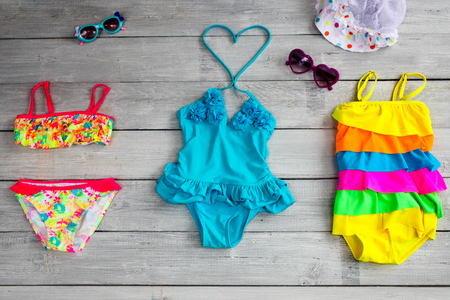 beachfront: Beautiful children is bathing suits on a white wooden background.