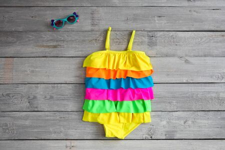 Het Badpak.Het Badpak Van Mooie Kinderen Zwempak En Zonnebril Op Een Witte