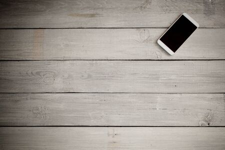 old desk: smart phone on an old wooden desk Stock Photo