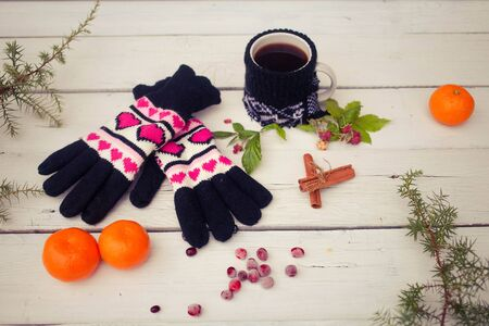 Gloves, cup of coffee on a white wooden background