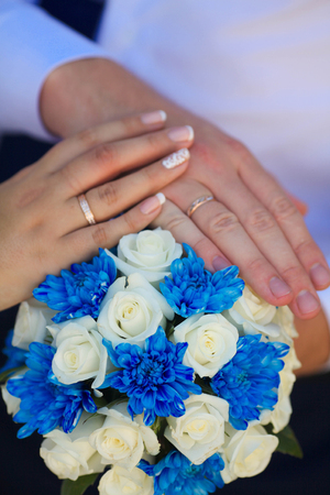 Hands of the groom and the bride with wedding rings and a wedding bouquet . Two wedding rings and spring blossoms. Wedding concept.