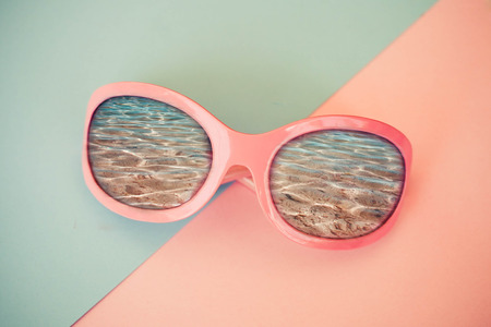 The fashion pink sunglasses reflecting the sea in a pink and blue background, pastel shades.