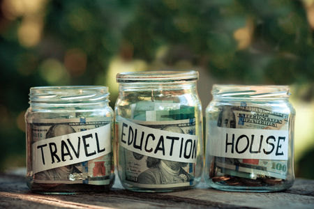 Glass jars with dollars and text: house, travel, education. Reklamní fotografie