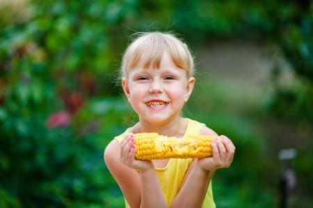 The cheerful girl eats corn on a farm.