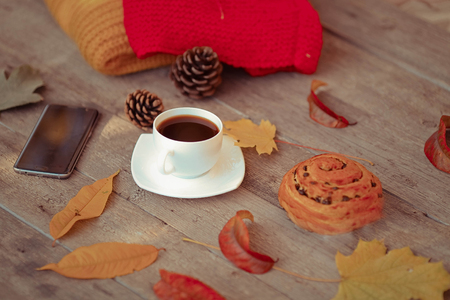 Cup with coffee, knitted warm clothes, autumn leaves and the smartphone on an old wooden background. Autumn on the concept. Reklamní fotografie