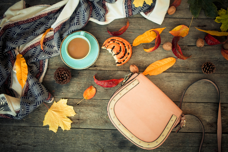Autumn leaves, coffee, roll, clothes and bag on an old wooden background. Autumn sale.