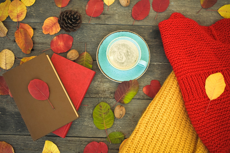 Autumn concept. Knitted sweaters, books, coffee and autumn leaves on a wooden background.
