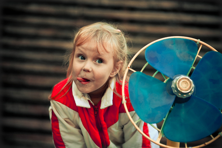 The retro the girl puts out the tongue, near the old fan