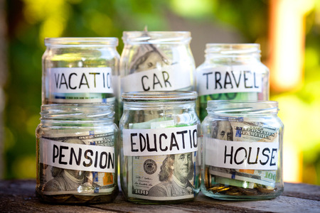 A lot coins in glass money jar on the wood table. Saving for house, health, education, car  and travel concept.