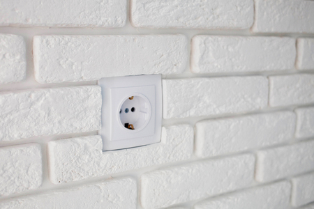 The white socket on a brick plaster wall.