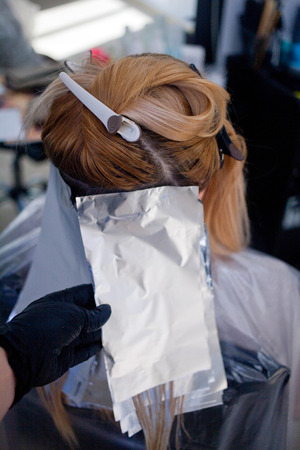 Coloring blondes in the beauty salon with paint and foil.