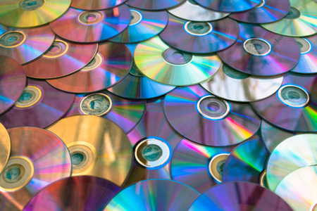 Background on the wall with old damaged discs cd. Stock Photo