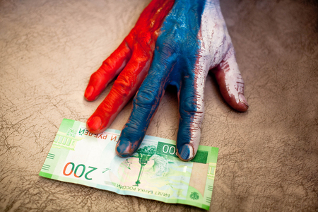 The male hand with the drawing of a flag of Russia reaches for money of 200 rubles with the image of the Crimea