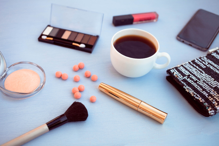 makeup Brush, powder, shadows and bag on a blue background