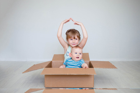 The girl with the little brother sit in a box, the concept of moving represents hands the rooftop. The place for the text, copy space. Reklamní fotografie