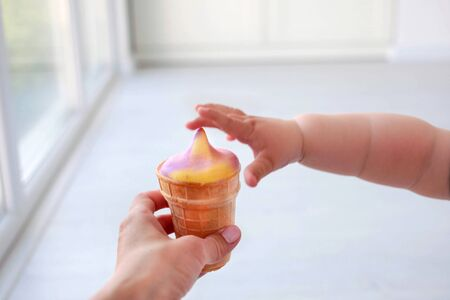 The children is hand reaches for ice cream, close up Banco de Imagens