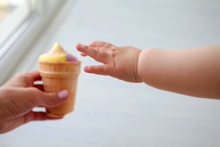The baby is hand reaches for multi-colored to ice cream, close up Banco de Imagens