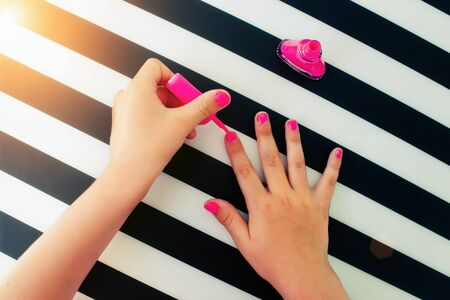 The little girl paints nails pink nail varnish. Top view