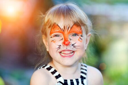 Portrait of funny girl with face painting on blurred background Stockfoto