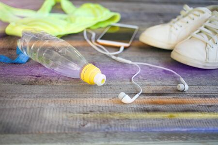 White sneakers, sportswear, water and a smartphone with headphones on a wooden background. Sports Accesories. Side view.