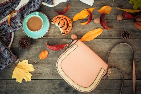 Women is bag, coffee and roll with autumn leaves and cones on a wooden background.