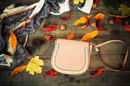 Close up a women is bag and autumn leaves on a wooden background .  Top view Stockfoto