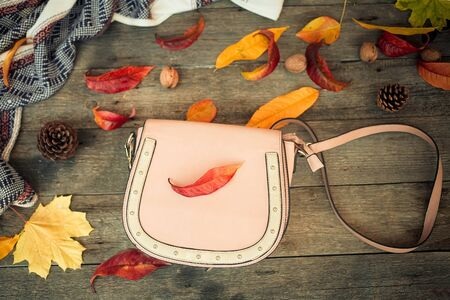 Close up a women is bag and autumn leaves on a wooden background .