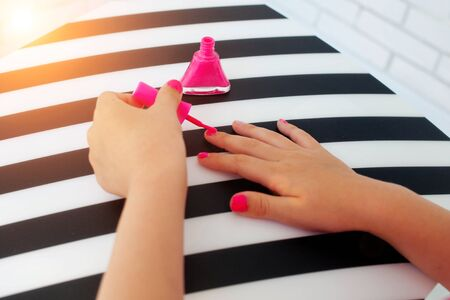 Hands of the little girl paint nails pink nail varnish on striped is black a white background. Side view