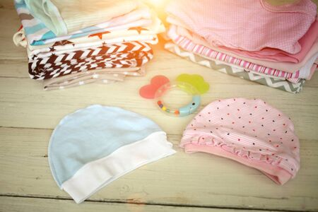 Clothes for the newborn boy and girl on a white wood background and son at sunset . Stockfoto