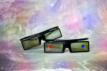 Two plastic 3 d glasses lie on each other onon the colorful background, with