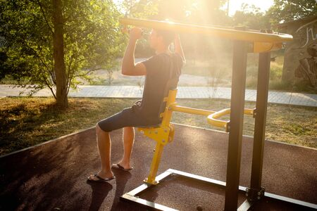 The man is engaged on the exercise machine, swings hands on the city street. Bright sunset. Horizontal Stok Fotoğraf