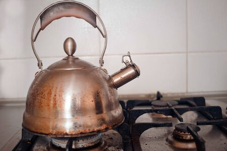 The dirty metal teapot is installed on the gas stove, a side view.
