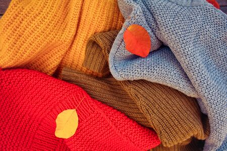A pile of different-colored knitted things and autumn leaves. Foto de archivo