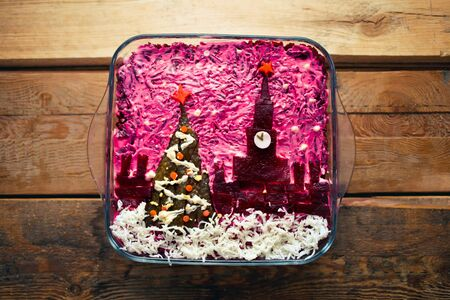 Home New Year is herring salad under a coat with the decoration of the Russian Kremlin and a tree on a wooden background. Russian cuisine.