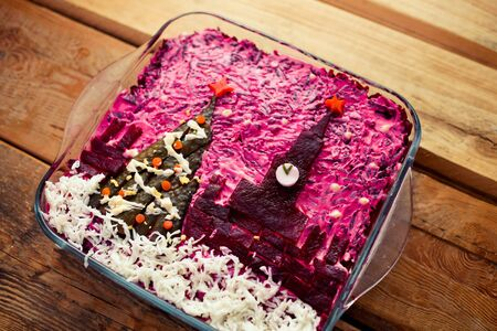 Home New Year is herring salad under a coat with the decoration of the Russian Kremlin and a tree on a wooden background. Russian cuisine. Side view.