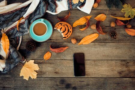 Smartphone, cup with coffee and a bitten bun on a wooden background with autumn leaves. Autumn concept. Top View. The concept of delivering food to the house. Stok Fotoğraf