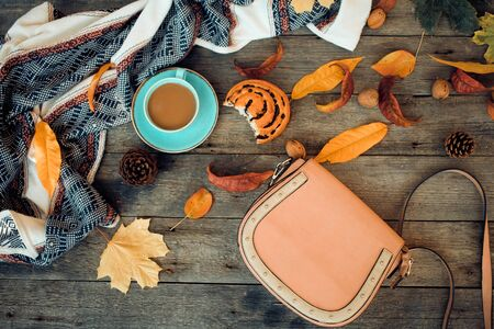 A woman is bag, a cup of coffee and a bun on a wooden background among the autumn leaves. The concept of autumn walks and shopping.